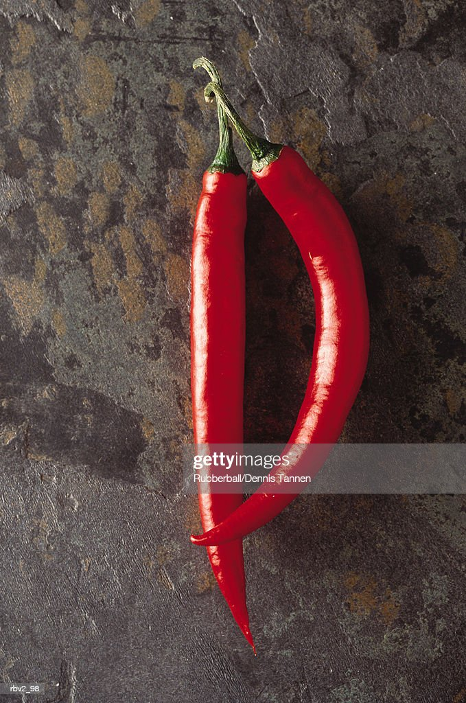 two red hot chili peppers lie on a stone background : Foto de stock