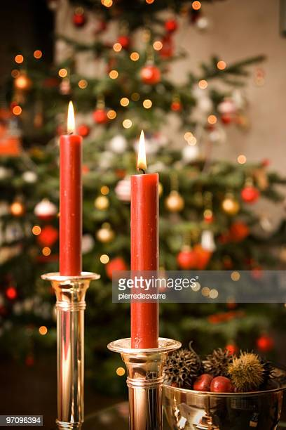 Two red lit candles with a Christmas tree in the background
