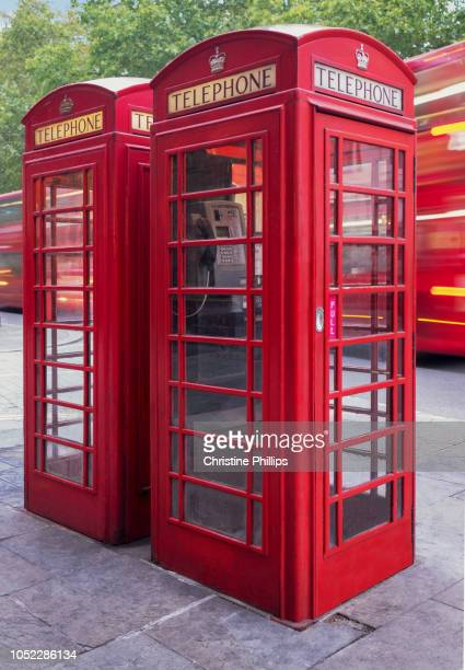 two red london phone booths and a london bus - english culture stock pictures, royalty-free photos & images