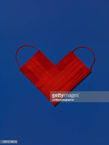 two red medical face masks shaped as a heart isolated on blue background - love stock pictures, royalty-free photos & images