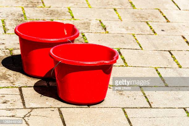 two red plastic buckets with metal handles - バケツ ストックフォトと画像