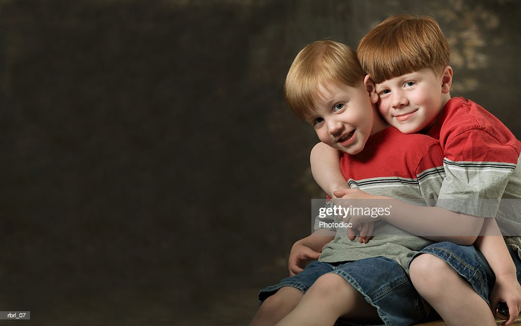 two redheaded brothers dressed in shorts and red and grey shirts hug each other : Foto de stock