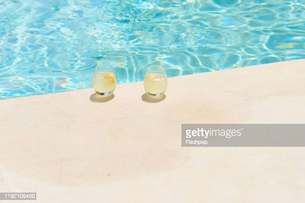 two refreshing drinks sat poolside - piscine photos et images de collection