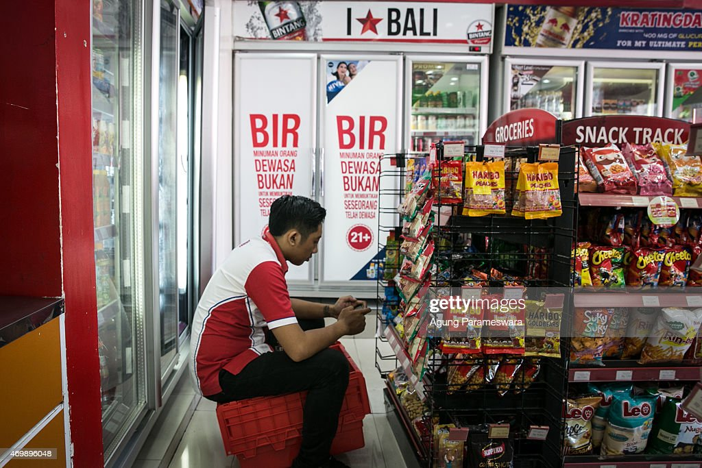 Two refrigerators that contain beer which are covered with a white banner are seen at Circle K, while the worker of Circle K sits and holds his smartphone on April 16, 2015 in Kuta, Bali, Indonesia. Indonesia, on April 16, banned small retailers from selling beer which is proposed that legislation by two Islamic parties-the Prosperous Justice Party and the United Development Party-that would ban all consumption of alcoholic drinks and bring jail terms of up to two years for offenders in Indonesia, home to the world's largest Muslim population. The regulation states that it is needed to protect public morals and culture and to improve the control and supervision of alcohol production, distribution and sales. There had been particular anxiety about how the ban might affect tourism on the Hindu-majority resort island of Bali. However, Indonesian trade minister Rachmat Gobel, who was shouted at during an ill-tempered meeting with community leaders in Bali last weekend, has now pledged to ease the restrictions on the island to ensure street vendors can still sell beer at the beach.