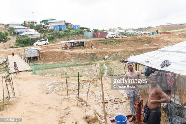 Kutupalong Ukhiya near Cox´s Bazar Bangladesh October 15 2018 Two refugee Rohingyas wash themselves with soap in the camp in front of a hut built by...