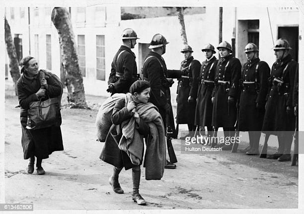 Two refugees made homeless during the civil war in Spain carry their possessions in small bags as they pass a group of French guards
