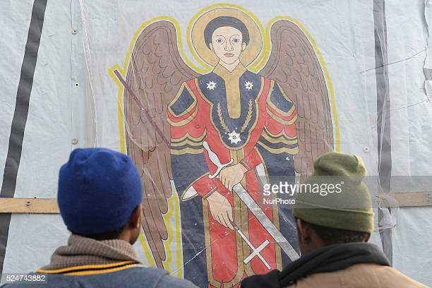 Two refugees praying to Archangel Gabriel outside the Ethiopia and Eritrea Community Church in the Jungle camp Calais France on Saturday 19 December...