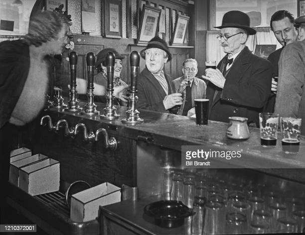 Two regulars 'Old Kate' and Wiiliam Say talking to Alice the barmaid at The Crooked Billet pub in Tower Hill London 1939 Kate is an office cleaner...