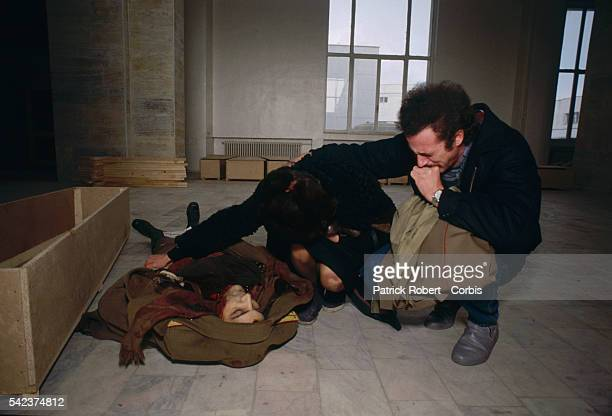 Two relatives mourning the death of a loved one whose corpse lies on the floor of the Forensic Institute in Bucharest which served as a morgue during...