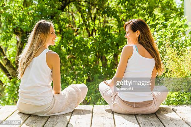 Two relaxed women sitting on wooden terrace