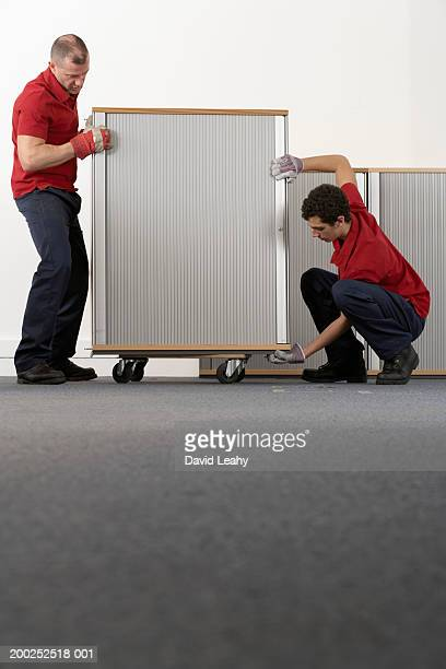 Two removal men positioning cabinet on wheels, ground view