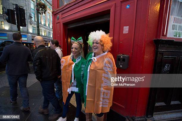 Two Republic of Ireland football fans draped in flags pictured outside a bar at Glasgow Cross before the European Championship qualifying match...