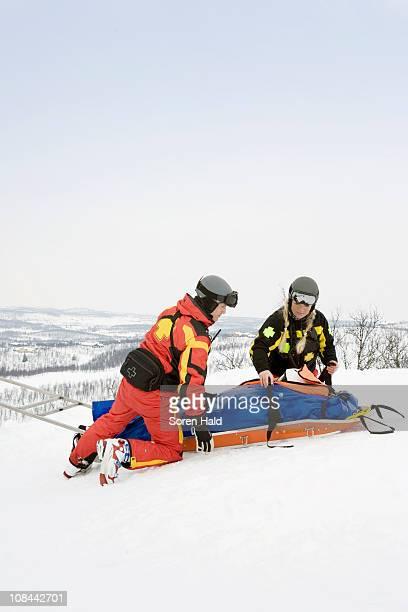 two rescuers helping skier - redding sporten stockfoto's en -beelden