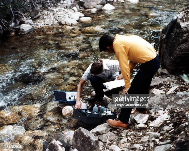 Two researchers collect water samples from a stream in the Ruby Mountains Elko County Nevada 1975 Image courtesy US Department of Energy