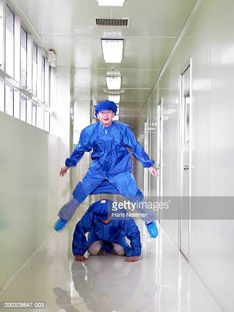 two researchers in protective smocks playing leapfrog in hallway - shoe covers stock pictures, royalty-free photos & images