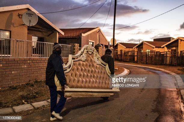 Two residents carry the headboard of a large bed as they transport it along a street in the Kwazakele township in Port Elizabeth, on July 11, 2020.