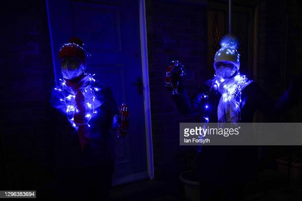 Two residents from the same household wear fairly lights as they take part in the Clap for Heroes event on January 14, 2021 in Saltburn-by-the-Sea,...