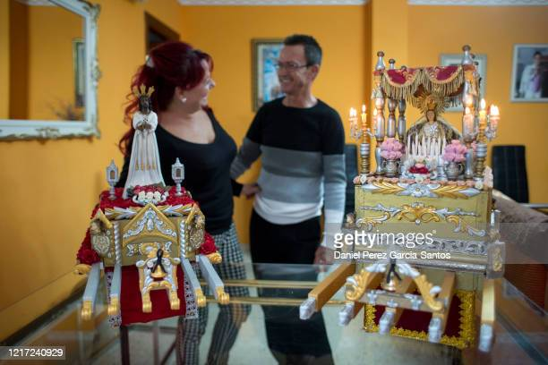 Two residents of the La Trinidad neighborhood prepare two miniatures of the Cristo Cautivo and the Virgen de la Trinidad during Holy Week while the...