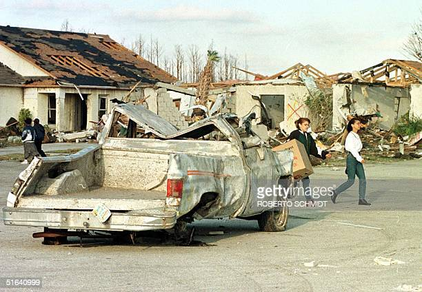 Two residents of the Lakeside residential complex in Kissimmee Florida walk past damaged houses and destroyed pickup truck after a tornado ripped...