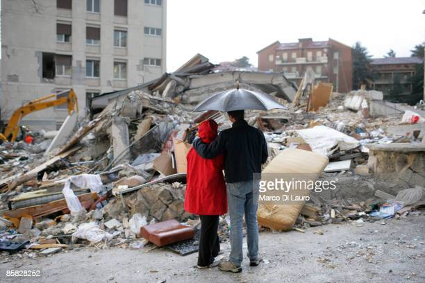 Two residents stand under an umbrella as they look at the ruins of their home after an earthquake on April 6, 2009 in L'Aquila, Italy. The 6.3...