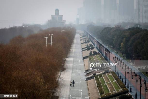 Two residents walk in an empty Jiangtan park on January 27, 2020 in Wuhan, China. As the death toll from the coronavirus reaches 80 in China with...