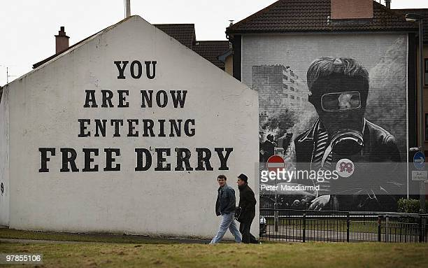 Two residents walk past Free Derry Corner in the Catholic Bogside area of Derry on March 15, 2010 in Northern Ireland. The Bloody Sunday Inquiry...