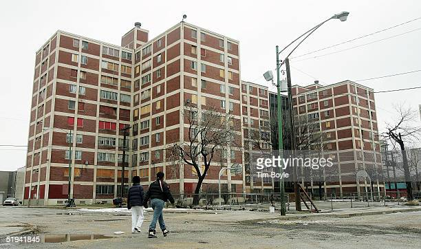 Two residents walk past one of the few remaining Chicago Housing Authority CabriniGreen public housing buildings January 12 2005 in Chicago Illinois...