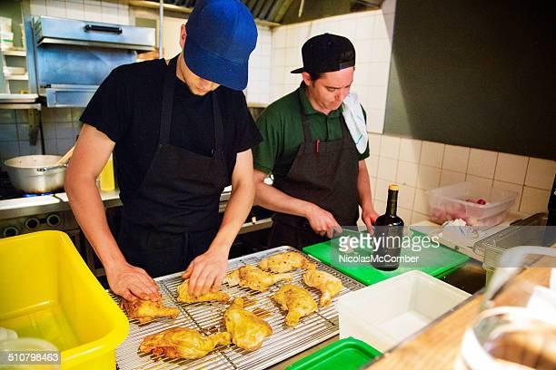 Two restaurant chefs preparing chicken