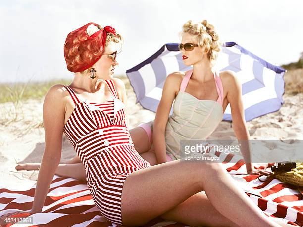 two retro young women on beach - women sunbathing stock photos and pictures