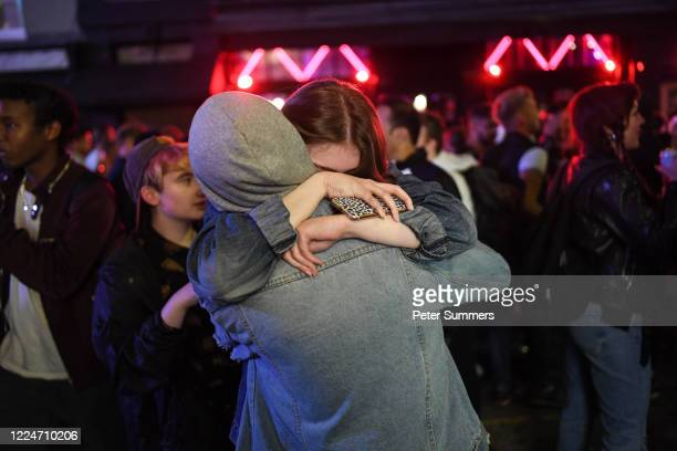 Two revellers are seen hugging outside a pub in Soho on July 4, 2020 in London, United Kingdom. The UK Government announced that Pubs, Hotels and...