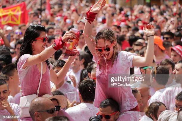 Two revellers douse themselves with wine as they celebrate the 'Chupinazo' to mark the kickoff at noon sharp of the San Fermin Festival in front of...