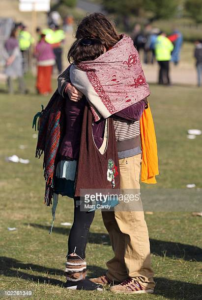 Two revellers embrace as the midsummer sun rises just after dawn over the megalithic monument of Stonehenge on June 21 2010 on Salisbury Plain...