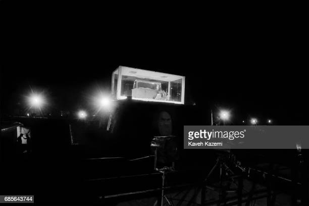 Two Revolutionary Guards chat at nighttime near the body of Ayatollah Khomeini seen inside a climatecontrolled glass box lit by spot lights Tehran...