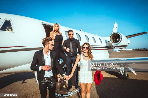 two rich and famous couples exiting a parked private jet parked on an airport tarmac - high society stock pictures, royalty-free photos & images