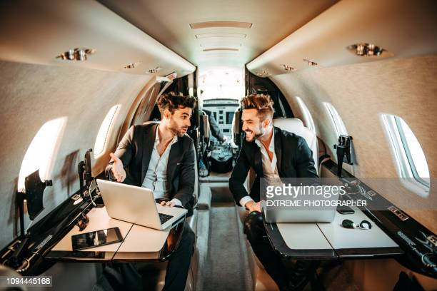 two rich businessmen working on the go together on a private airplane - side by side stock pictures, royalty-free photos & images