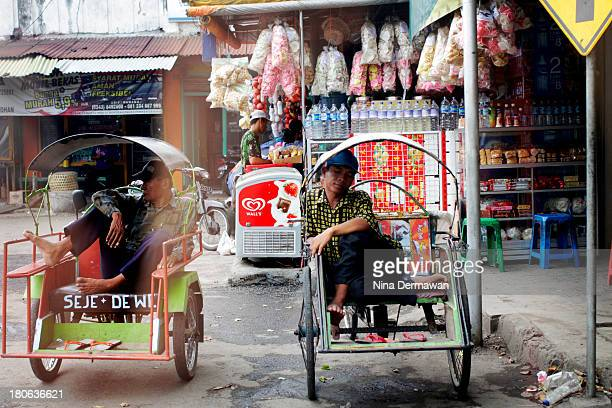 Two ricksaw drivers, parked on the street-side, seemed to be enjoying their break, relaxing while waiting for their next customers.