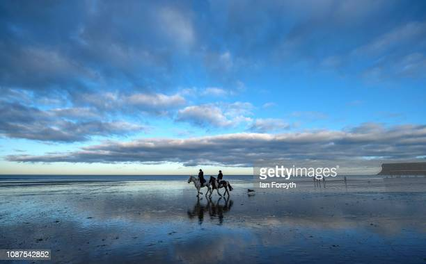 Two riders canter at low tide along the wide expanse of Saltburn beach on December 28 2018 in Saltburn By The Sea England Unseasonably mild weather...