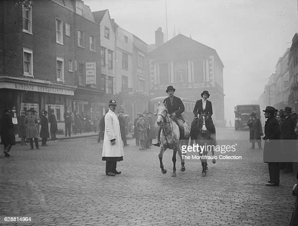 Two riders G T W Brig and Miss Pat Campbell trotting through the streets of Windor watched by a crowd of people on their horses having just completed...