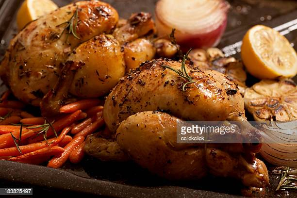 Two roasted chicken with baby carrots, onion and lime