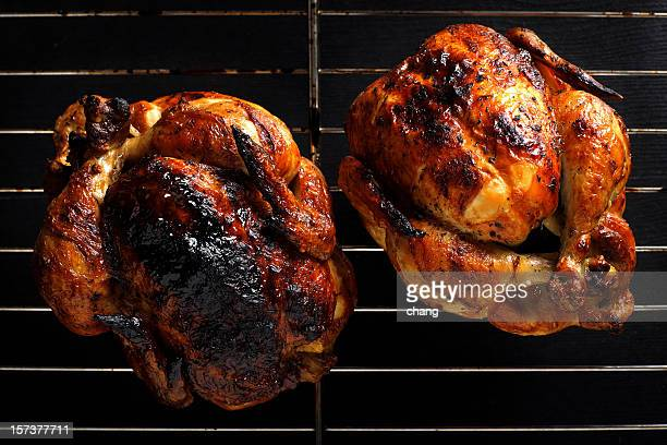 Two roasted chickens still on the grill