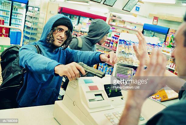 two robbers threatening a shop assistant with a gun - convenience store counter stock photos and pictures