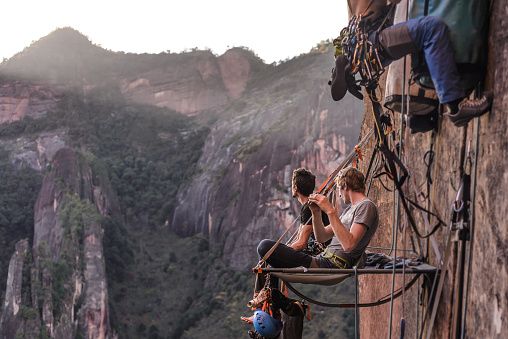 Two rock climbers sitting on portaledge, looking at view, Liming, Yunnan Province, China - gettyimageskorea