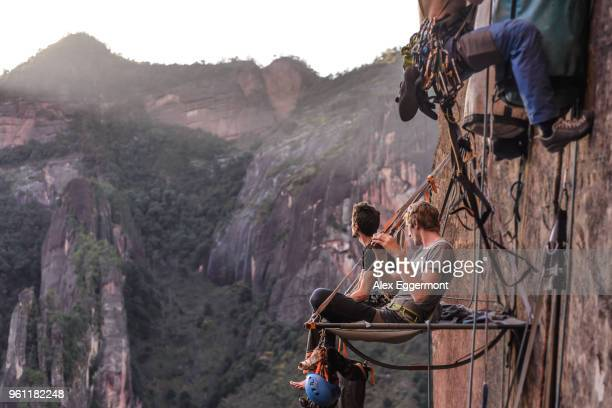Two rock climbers sitting on portaledge, looking at view, Liming, Yunnan Province, China