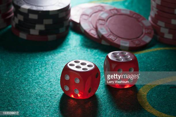Two rolled sixes on a craps table, gambling chips in the background