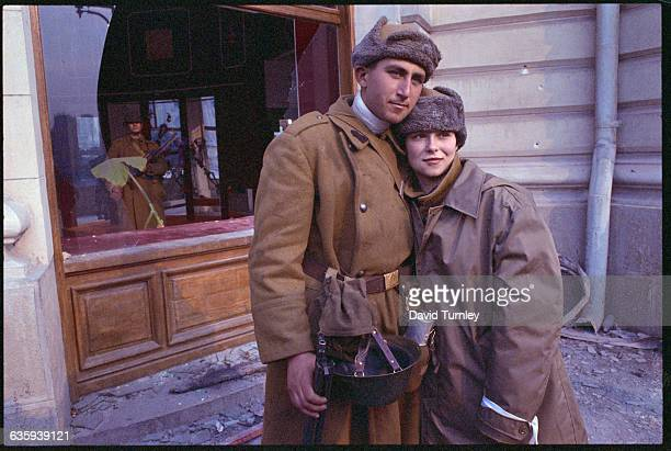Two Romanian soldiers man and woman hug and look happy and relieved at the overthrow of Communist dictator Nicolae Ceausescu