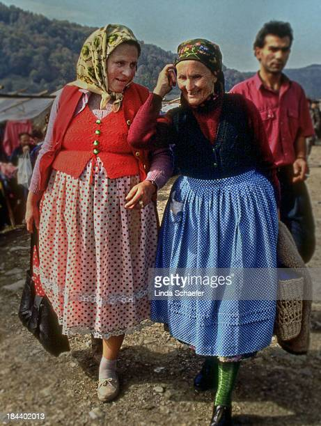 Two Romanian women shopping at an outdoor market in Western Romania. They are both wearing traditional skirts and scarfs. This was shortly after the...