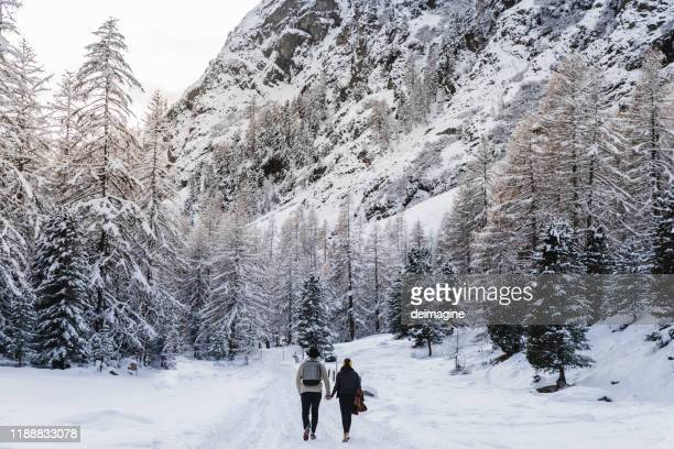 two romantic hikers hand in hand in snowy covered forest - switzerland stock pictures, royalty-free photos & images