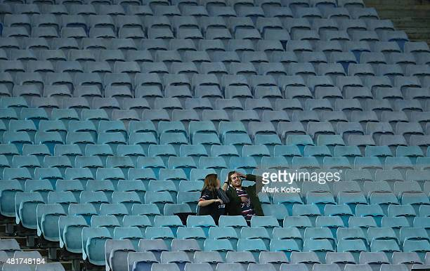 Two Roosters supporters in the crowd watch on during the round 20 NRL match between the Wests Tigers and the Sydney Roosters at ANZ Stadium on July...