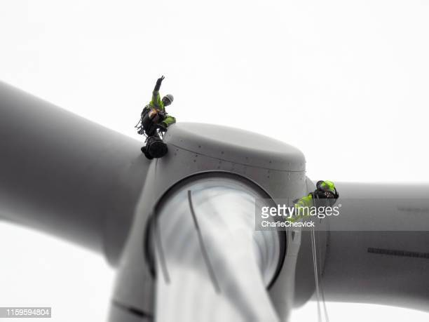 two rope access technician doing blade inspection on wind turbine and doing gesture - high up stock pictures, royalty-free photos & images