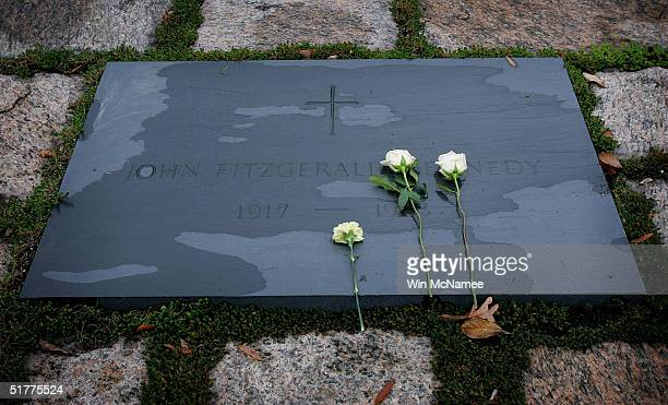 Two roses and a carnation lay atop the gravesite of former US President John F Kennedy at Arlington National Cemetery in Arlington Virginia November...